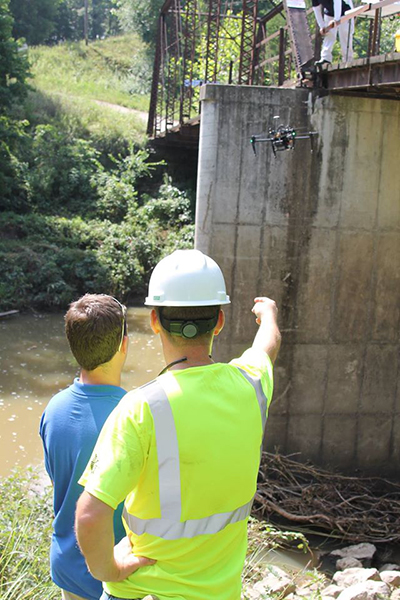 Two men stand in the foreground while piloting a drone near a bridge for inspection