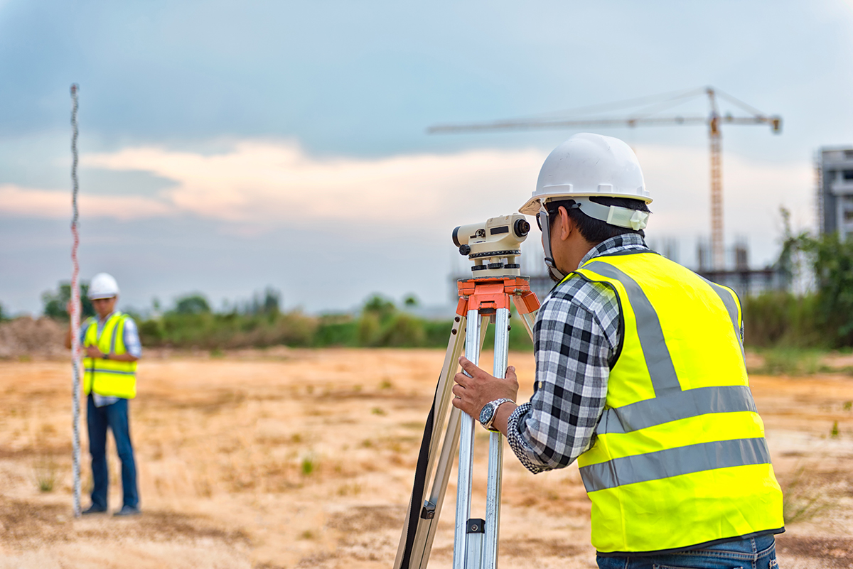 Route surveying crew works on survey in a field for a future transmission line