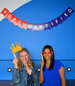 Two McClure employees pose under 'GPTW Certified' sign